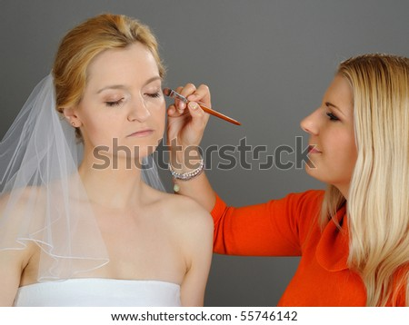 Natural Wedding make-up is being applied to pretty bride. gray background