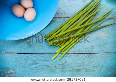 Natural white eggs in a blue bowl and Spring onions over dingy blue wooden table.  - stock photo