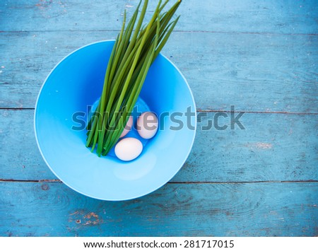Natural white eggs in a blue bowl and Spring onions over dingy  blue wooden table. Top view - stock photo