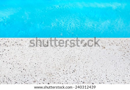 Natural white porous stone swimming pool edge close up. Calm blue water. Selective focus on hard stone edge. Room for text, copyspace.  - stock photo