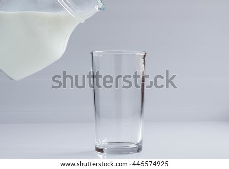 Natural whole milk in a jug and a glass