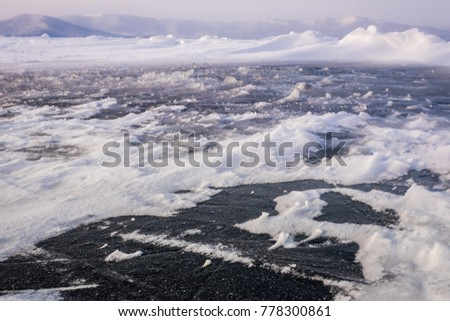 Natural winter lake ice breaking with clear sky background, selective focus. Frozen mountain lake with blue ice and cracks on the surface. Winter landscape with snowy hills under a blue sky.