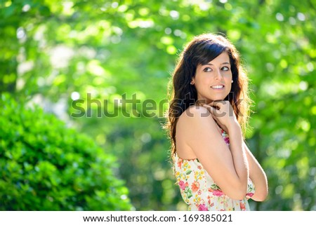 Natural woman looking shy. Brunette girl on sunny spring or summer day in park. - stock photo