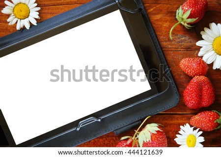 Natural wooden background with fresh strawberries and the tablet with a white screen - stock photo