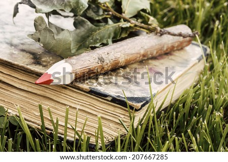 natural wooden pencil and old book with green leaves in the grass - ecological theme natural wooden pencil with green leaf  - stock photo
