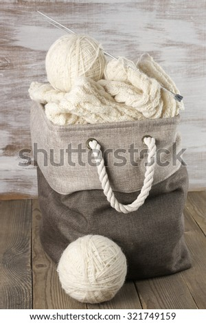 Natural woolen yarn and knitting in fabric basket on rustic wooden floor. - stock photo