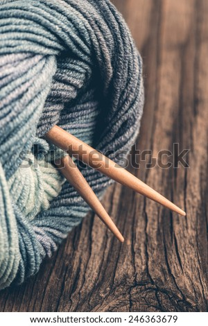 Natural woolen yarn and knitting on vintage wooden background. - stock photo