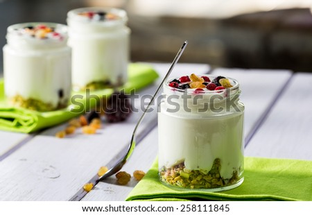 Natural yogurt with fresh berries and grains - stock photo
