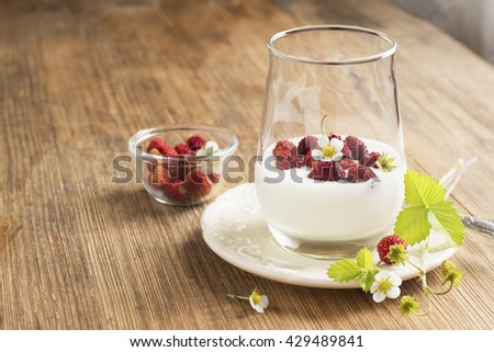 Natural yogurt with fresh strawberries for breakfast served in portions in a glass on a wooden background. The concept of a healthy natural food. selective focus - stock photo