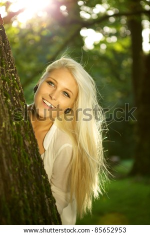 Natural young beauty hiding behind a tree. Sun is shining. - stock photo
