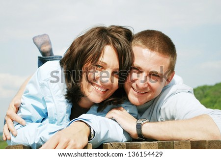 Natural young couple laughing at outside. - stock photo