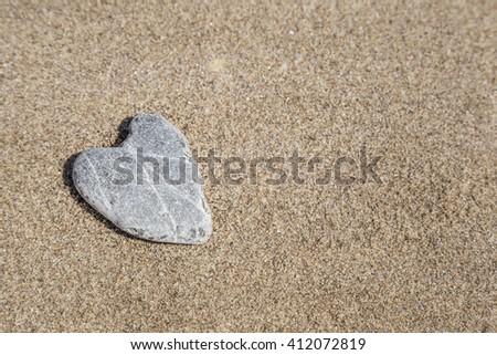 naturally heart shaped stone on sand - stock photo