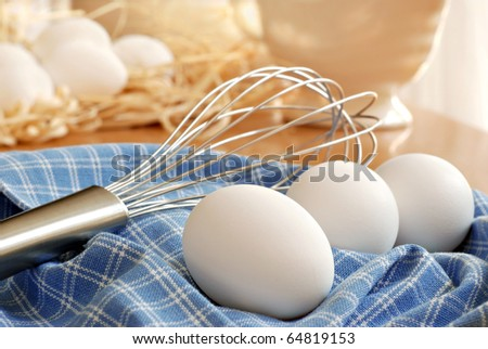 Naturally sunlit still life of fresh eggs with whisk on kitchen table.  Eggs with raffia in background.  Closeup with shallow dof. - stock photo