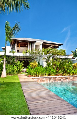 Naturaly decorated house  using fancy plants with a green lawn and a swimming pool with wooden path - stock photo
