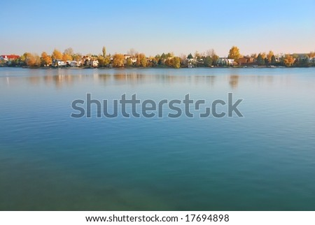 Nature autumn background with water surface and yellow trees
