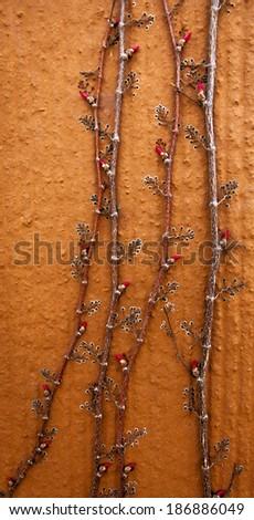 Nature Background - Creeping Shrub with Buds on Orange Wall - stock photo