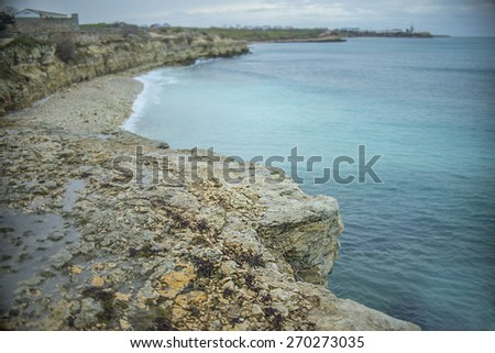 Nature background of Black sea wave Backdrop of  beach with mountains hill in perspective with blue sky and dramatic clouds Gray rainy day Water and stone texture  - stock photo