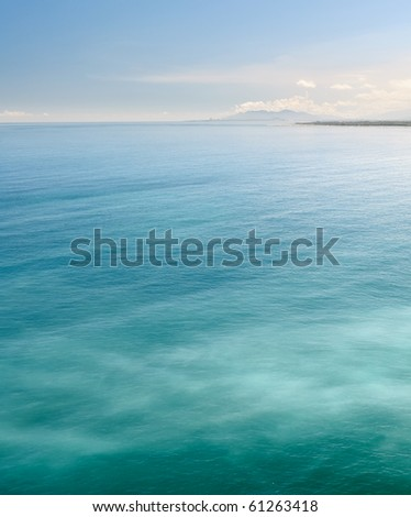 Nature background of sea with green ocean under blue sky. - stock photo