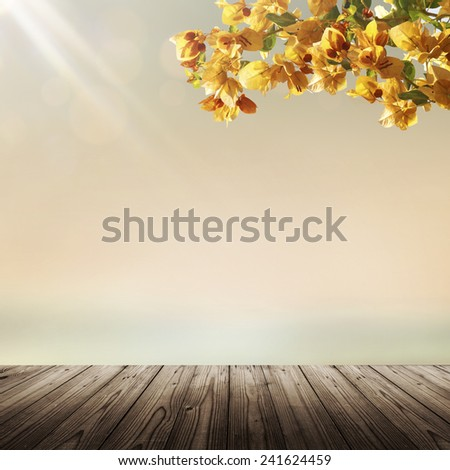 Nature background with empty wooden table, blooming flowers and blurry tropical beach and sea at sunset - stock photo