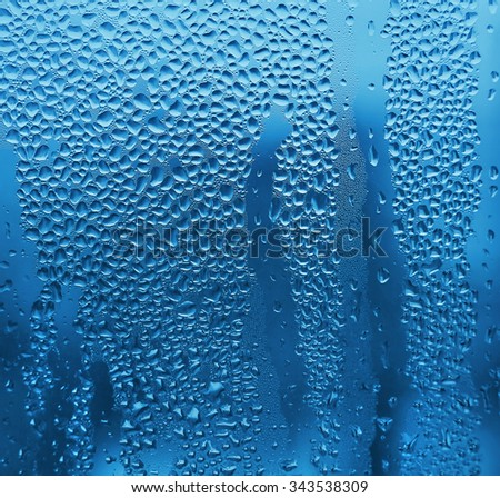 Nature blue background with water drops on glass