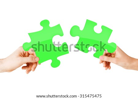 nature, ecology, energy saving and people concept - close up of couple hands trying to connect green puzzle pieces