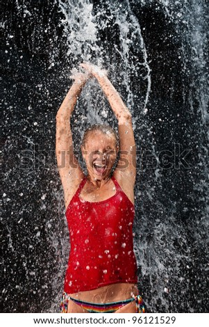 Nature emotion concept - Young and emotional girl in red tank-top enjoying jungle waterfall - stock photo