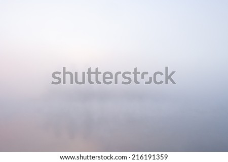 Nature foggy (misty) background: trees and their reflections in water surface (lake, river, pond) visible through fog (mist) at morning. Colors are light pink and light blue. Can be used as wallpaper. - stock photo
