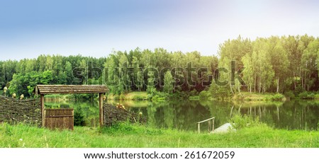 Nature landscape panorama. Wooden rural yard near lake in forest at summer day. - stock photo