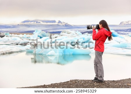 Nature landscape photographer taking picture photos with SLR camera on Iceland Jokulsarlon glacial lagoon / glacier lake. Woman taking photograph of beautiful Icelandic nature with Vatnajokull. - stock photo