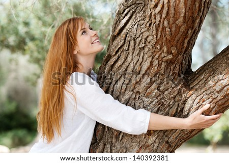 Nature lover concept with a beautiful young girl standing embracing a tree trunk with a smile of pleasure - stock photo