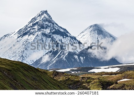 Nature of Kamchatka - beautiful volcanic landscape: view on Kamen Volcano, active Kliuchevskoi Volcano and active Bezymianny Volcano. Russia, Far East, Kamchatka. - stock photo