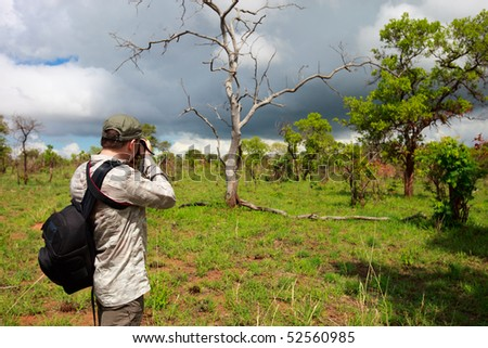 Nature photographer taking photos on safari in Tanzania - stock photo