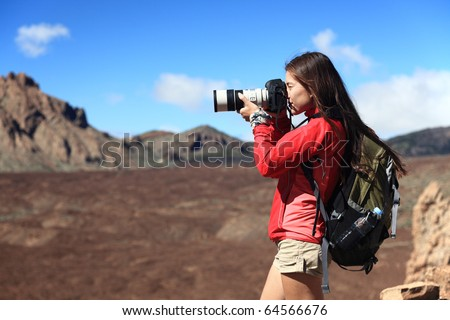 Nature Photographer taking pictures outdoors during hiking trip on Teide, Tenerife, Canary Islands. - stock photo