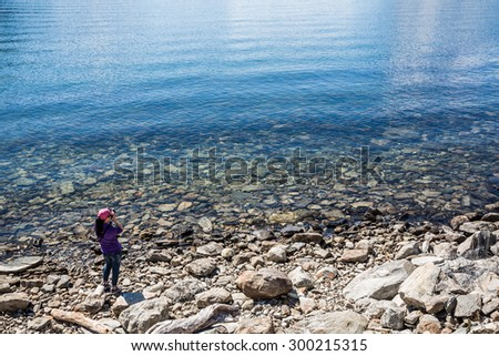 Nature photographer tourist with camera shoots lake. Beautiful Nature Norway. - stock photo