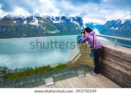 Nature photographer tourist with camera shoots. Stegastein Lookout. Beautiful Nature Norway. - stock photo