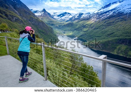 Nature photographer tourist with camera shoots while standing on top of the mountain. Beautiful Nature Norway. - stock photo