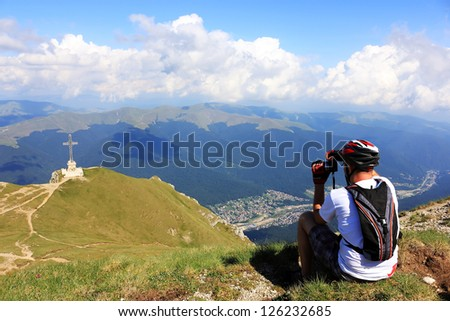 Nature photographer with digital camera on top of the mountain - stock photo