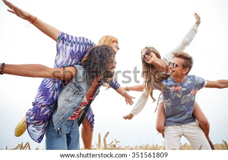 nature, summer, youth culture and people concept - happy young hippie friends having fun on cereal field - stock photo