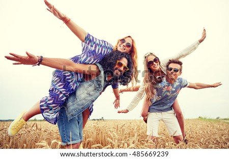 nature, summer, youth culture and people concept - happy young hippie friends having fun on cereal field