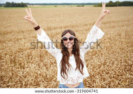 nature, summer, youth culture and people concept - smiling young hippie woman in sunglasses on cereal field - stock photo