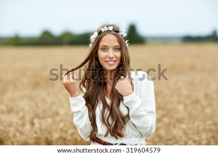 nature, summer, youth culture and people concept - smiling young hippie woman wearing flower wreath on cereal field - stock photo