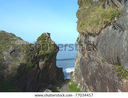 Nature trail leading between the cliffs down to the shore - stock photo