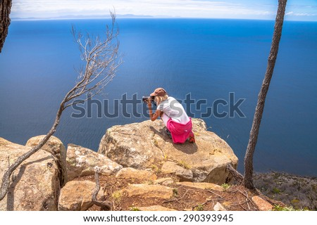 Nature travel photographer woman taking pictures on a spectacular cliff during the trekking Fluted Cape Within the South Bruny National Park Bruny Island, Tasmania Australia. - stock photo