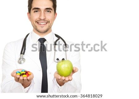 Nature vs Science. Young male doctor holding out an apple and medications in his hands smiling to the camera isolated on white  - stock photo
