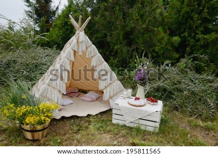 nature white tent on a bouquet of flowers and a box strawberries and milk - stock photo