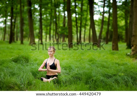 Nature yoga session in beautiful green polish woods, between trees. Meditation - namaste in lotus pose. Healthy lifestyle concept - stock photo