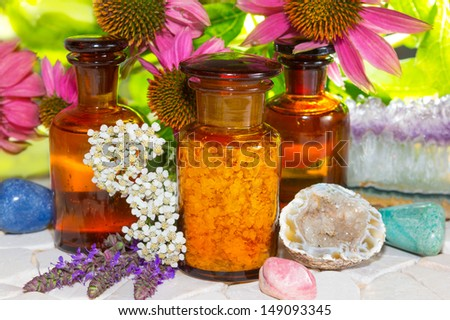 Naturopathy with gemstones for crystal healing and flowers including lavender and echinachea for alternative medicine with essential oil , plant extracts and dried plants for aromatherapy - stock photo