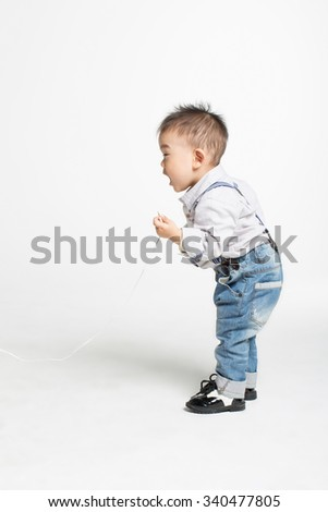 naughty asian chinese baby, holding MP3 wires loud cry in white studio - stock photo