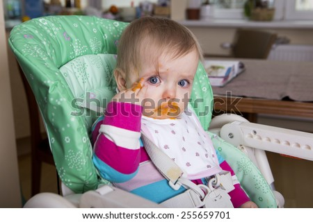Naughty baby eating alone in the high chair. Dirty face - stock photo