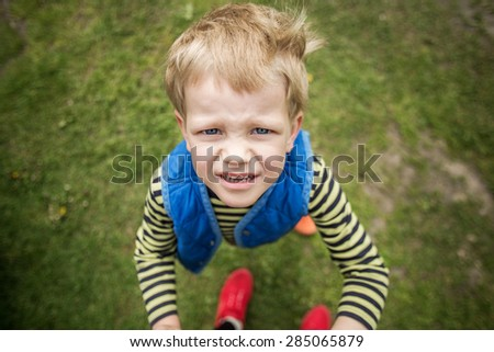 Naughty boy looking up. Outdoor portrait. Close up - stock photo